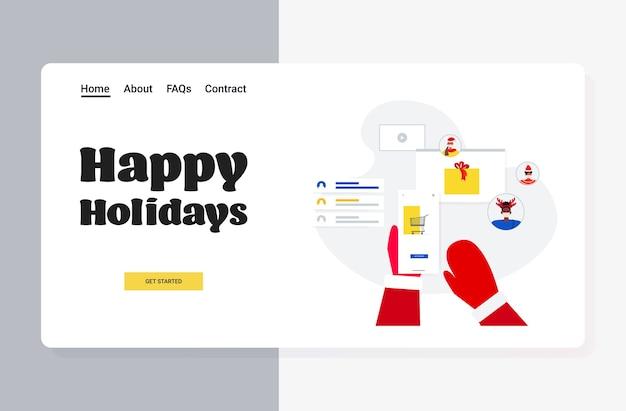 スマートフォンのオンラインショッピングを使用してサンタクロースの手新年あけましておめでとうございますメリークリスマスの休日のお祝いのコンセプトのランディングページ