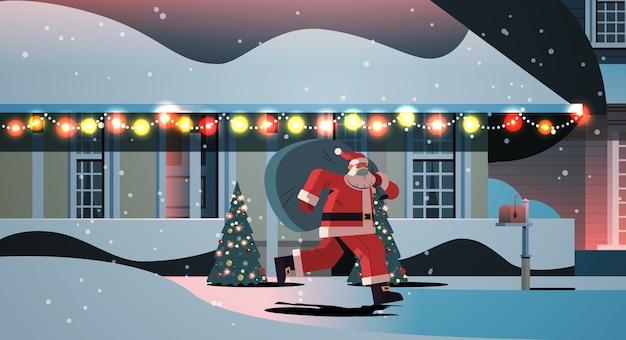 贈り物でいっぱいの袋で実行されているマスクのサンタクロース新年あけましておめでとうございますメリークリスマスの休日のお祝いのコンセプト夜冬の通り装飾された家の全長水平ベクトルイラスト