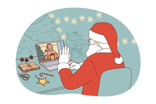伝統的な赤い衣装を着たサンタクロースが座って、ビデオ通話の遠方の会議中にラップトップで冬休みの幸せな子供を祝福します