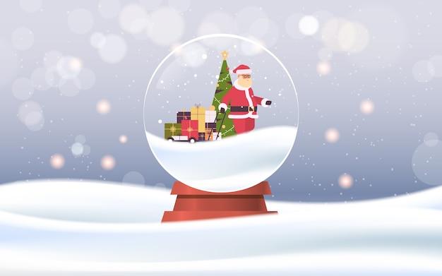 魔法のガラス玉のギフトボックスとトロリーカートを引っ張るサンタクロースメリークリスマス新年あけましておめでとうございます冬の休日のお祝いのコンセプト降雪