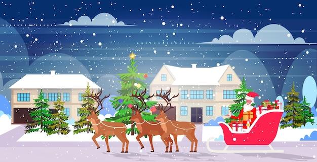 トナカイとそりに乗ってサンタクロースメリークリスマス新年あけましておめでとうございます冬の休日のお祝いのコンセプト雪に覆われた田園風景