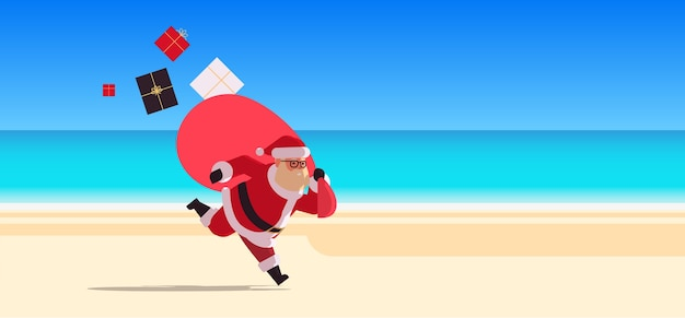 贈り物でいっぱいの大きな袋で実行されているサンタクロース新年あけましておめでとうございますクリスマス休暇休日のお祝いのコンセプト熱帯のビーチ海景背景全長フラット