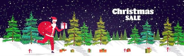 プレゼントいっぱいの大きな袋で走るサンタクロースメリークリスマス明けましておめでとうございます。