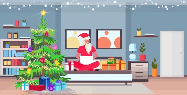 Santa claus sitting lotus pose on bad using laptop modern bedroom with fir tree and gift boxes merry christmas new year holidays celebration concept    illustration