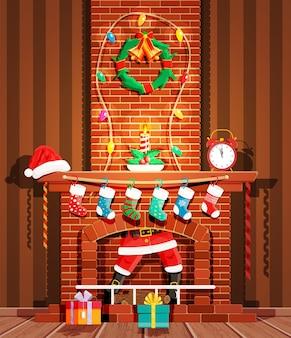 サンタクロースが煙突に引っかかった。靴下、キャンドル、ギフトボックス、花輪、花輪のある暖炉。明けましておめでとうございます。メリークリスマス休暇。新年とクリスマスのお祝い。ベクトルイラストフラットスタイル