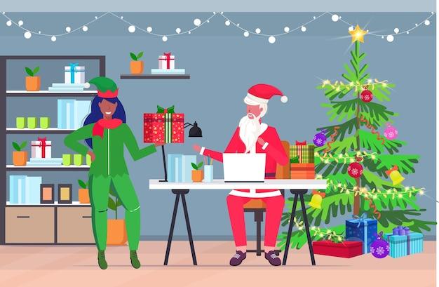 Santa claus using laptop female elf helper holding present gift box christmas new year holidays celebration concept modern office interior greeting card