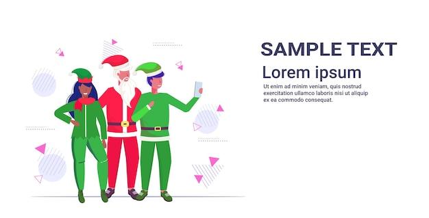 サンタクロースとミックスレースのエルフのカップルがスマートフォンのカメラで自分撮り写真を撮るクリスマス休暇お祝いコンセプトコピースペースイラスト