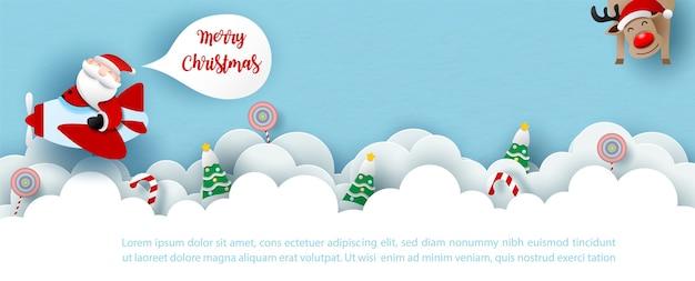 白い雲と青い背景の上のトナカイのクリスマスのシンボルのオブジェクトでプロペラ飛行機を運転するサンタクルース。ペーパーカットスタイルとバナーデザインのクリスマスグリーティングカード。