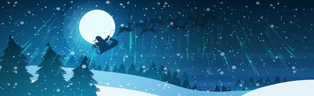 Санта, летающий в санях с оленями в ночном небе над заснеженными соснами, еловым лесом, с рождеством, с новым годом, концепция зимних праздников