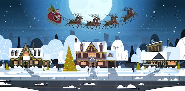 Santa flying in sledge with reindeers in sky over village houses, merry christmas and happy new year banner winter holidays concept