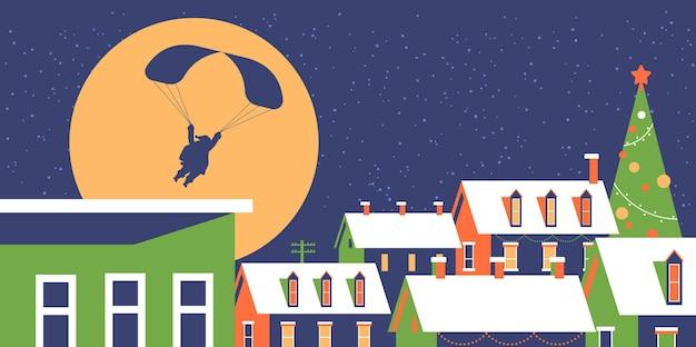 屋根に雪が降る雪の村の家の上に夜空にパラシュートで飛んでいるサンタメリークリスマス冬の休日コンセプトグリーティングカードフラット水平ベクトル図