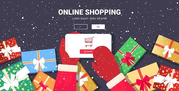 모바일 앱 온라인 쇼핑 개념을 사용하여 산타 손 크리스마스 휴일 축하 스마트 폰 화면 복사 공간 배너