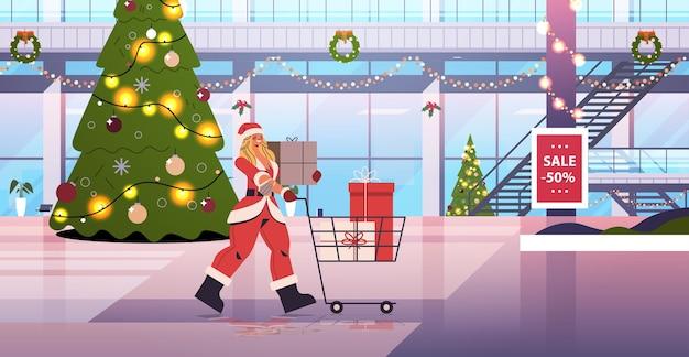 サンタの女性ギフトボックスでいっぱいのトロリーカートを押す新年あけましておめでとうございますメリークリスマスの休日のお祝いのコンセプトショッピングモールインテリア水平全長ベクトルイラスト