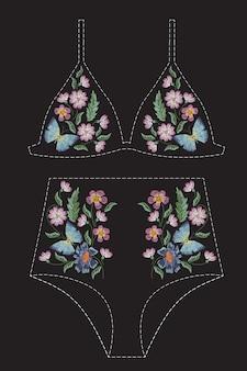 花と蝶のサテンステッチ刺繍デザイン。水着、ブラ、ビキニ、服のフォークライン花柄トレンディなパターン。黒の背景に服の自然なファッショナブルな飾り。