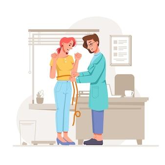 栄養士のオフィスでウエストを測定する満足のいくスリムな女の子は、体重を減らして食べることで素晴らしい結果をもたらします