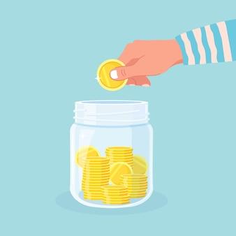 Сэкономьте деньги в стеклянной банке. рука бросить золотые монеты в копилку. накопительные вклады. инвестиции на пенсию. богатство, концепция дохода. наличные деньги падают в бутылку