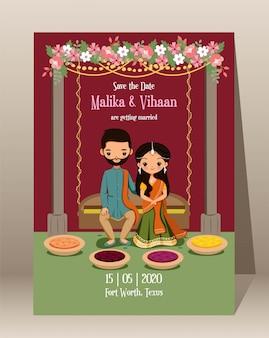 Сохраните дату. милый индийский жених и невеста с традиционной свадебной пригласительной картой