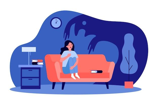 Испуганная женщина, сидящая на диване в одиночестве ночью