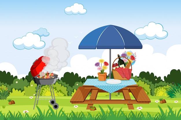 バーベキューグリルとピクニックテーブルの上の食べ物のシーン