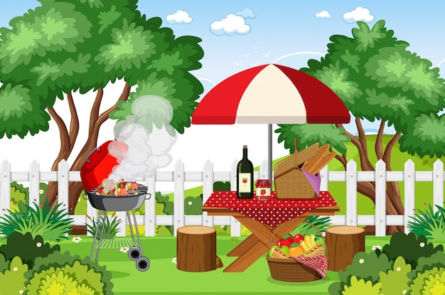 Scene with bbq grill and food on picnic table in the park