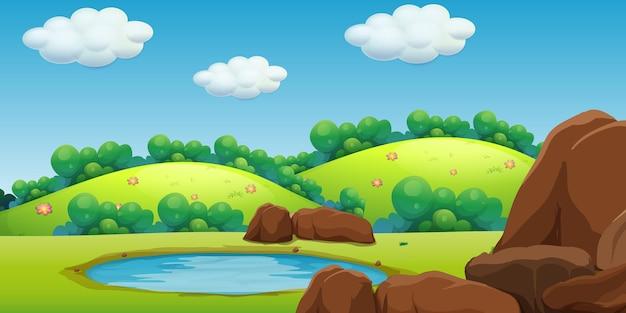 緑の山々と小さな池のあるシーン
