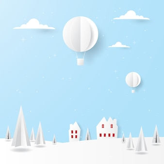 Scenery winter landscape, houses, pine trees and hot air balloon flying in the sky