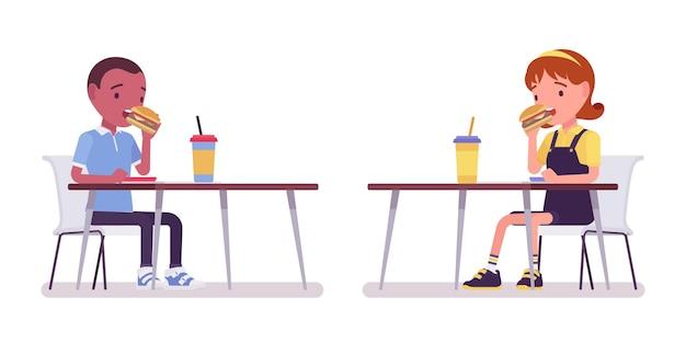 학교 소년과 소녀는 테이블에서 점심을 먹고