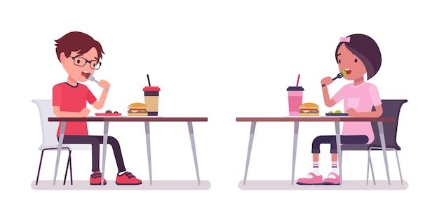 学校の男の子、食堂で昼食を食べて机に座っている女の子