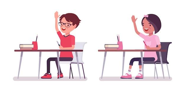 School boy, girl sitting at desk raising hand to answer