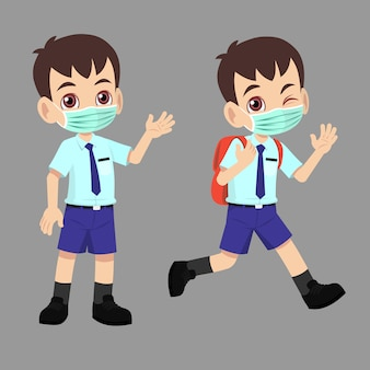 School boy in uniform going back to school with face mask and waved.