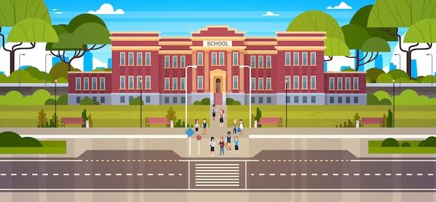 푸른 잔디와 나무 풍경과 앞 마당에 학생의 그룹과 학교 건물