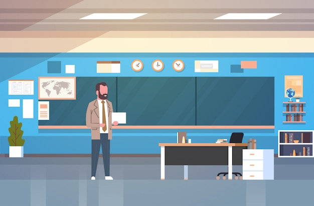 School classroom interior with male teacher standing over chalk board in class room