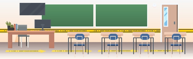 School classroom with signs for social distancing yellow stickers coronavirus epidemic protection measures