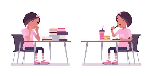 책상에서 공부하고 식사하는 여고생