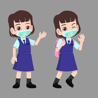 School girl in uniform standing and waved to going back to school with face mask