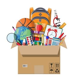 段ボール箱の中の学校のアイテム。さまざまな学用品、文房具。