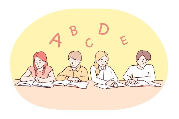 학교, 수업, 학습 문자 및 알파벳, 교육 개념. 책과 함께 앉아 교실에서 영어 알파벳의 편지를 배우는 긍정적 인 집중 어린이 급우 그룹