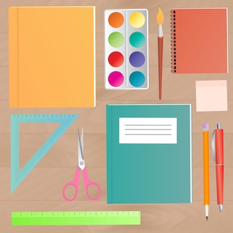 School supplies on a wooden work table top view.