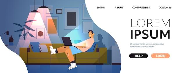 暗い夜のホームルームの水平方向の完全な長さのコピースペースでソファに横たわっているラップトップ画面のティーンエイジャーを見ている男子生徒