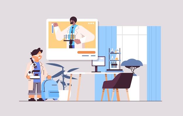 ビデオ通話の自己隔離オンライン通信中にウェブブラウザウィンドウで教師と化学実験を行う男子生徒