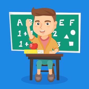 Schoolboy raising hand while sitting at the desk.