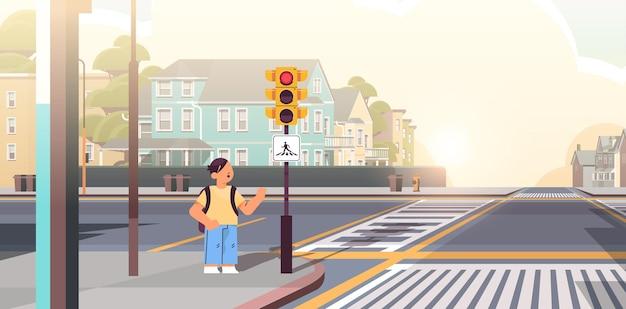 Школьник с рюкзаком ждет зеленого светофора, чтобы перейти дорогу на пешеходном переходе безопасность дорожного движения