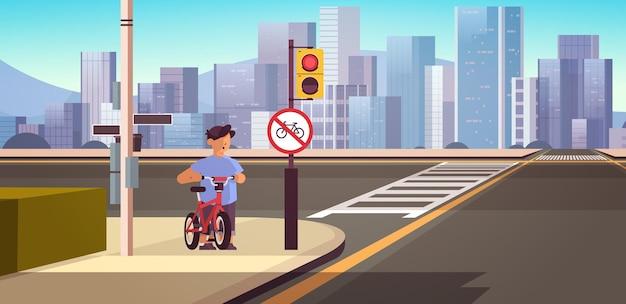 Школьник с велосипедом стоит возле красного круглого знака запрета на жидкое движение, безопасность дорожного движения