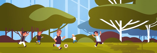 Schoolboys playing football elementary school kids having fun with soccer ball on grass sport activities concept landscape background flat full length horizontal