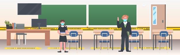 Schoolchildren in masks keeping distance to prevent coronavirus pandemic social distancing concept school classroom interior horizontal