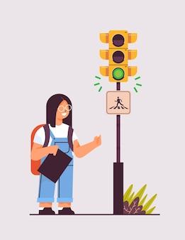 횡단 보도 도로 안전에 도로를 건너 녹색 신호등을 기다리는 배낭 여학생