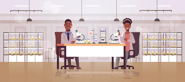 Пара ученых с помощью микроскопа
