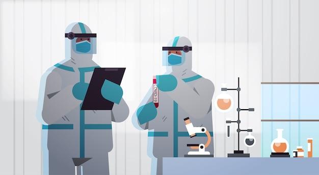 コロナウイルスと戦うためにワクチンを開発している科学者は、医療ラボのワクチン開発コンセプトの水平方向の図で働く防護服を着てカップルします