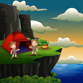 スカウトの男の子と女の子が崖の上にキャンプしています。