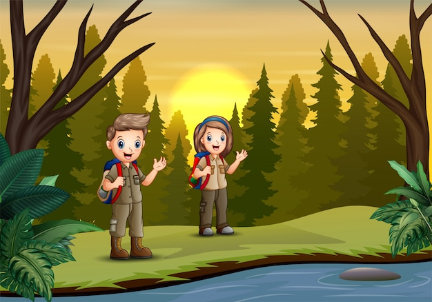 The scout boy and girl hiking in the forest
